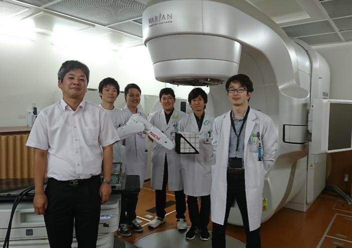 写真2:研究チームのメンバーと,提案システム(右端:椎木講師,左端:藤井准教授)